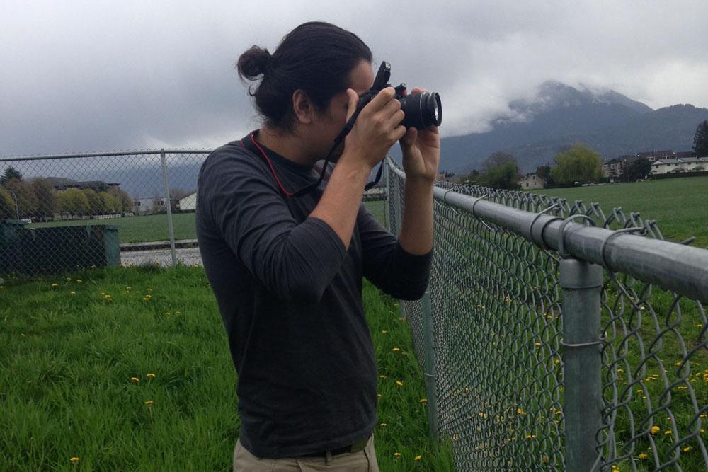 Jon Hernandez taking photos in the field in Sto:lo Nation
