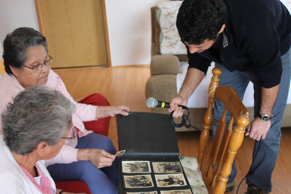 Peter Mothe looks at family photos with the Thomas sisters