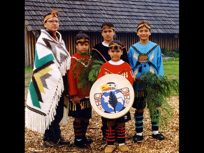 Willie Charlie (left) ran the first puberty camp in 1993. He and a group of boys from Warrior Camp stand in front of the Charlie Longhouse. Photo courtesy of James Leon.